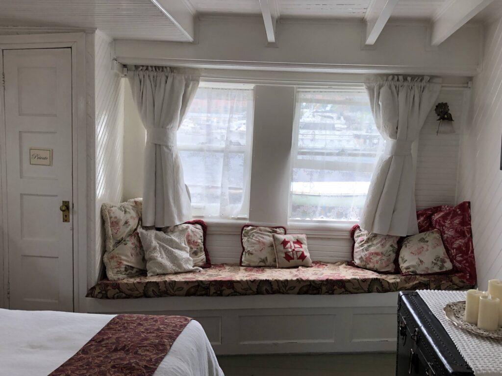 A bench seat in the master stateroom of Lotus beneath two windows