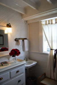 A sink and dresser with a window in a stateroom aboard the Lotus