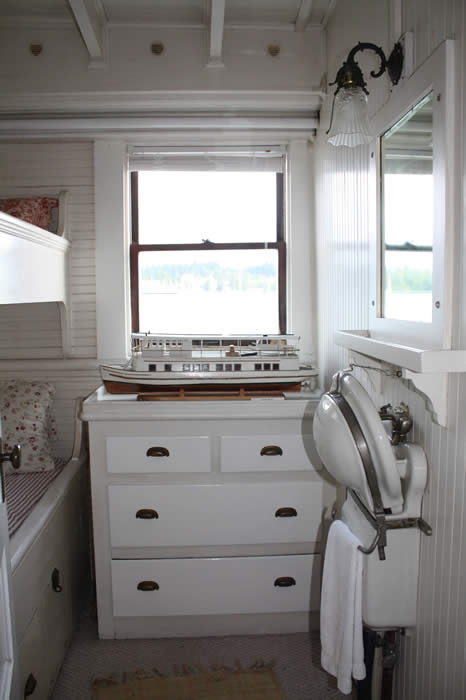 Pullman style sink in the up position, dresser drawers, window, and two bunks in a stateroom aboard the Lotus